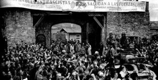 Prisioneros de Mauthausen saludan a la 11ª División Acorazada de los EE UU por su liberación bajo una pancarta escrita en español sobre sábanas.