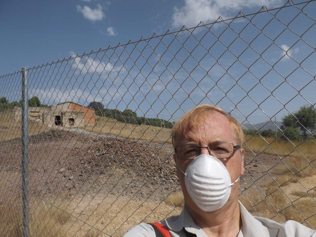 El autor de este reportaje, Pedro Pozas, con mascarilla junto a los residuos de arsénico. Los escombros de tonos grisáceos que se observan detrás son altamente peligrosos por contacto y por vía respiratoria. (Fotografía: Pedro Pozas).