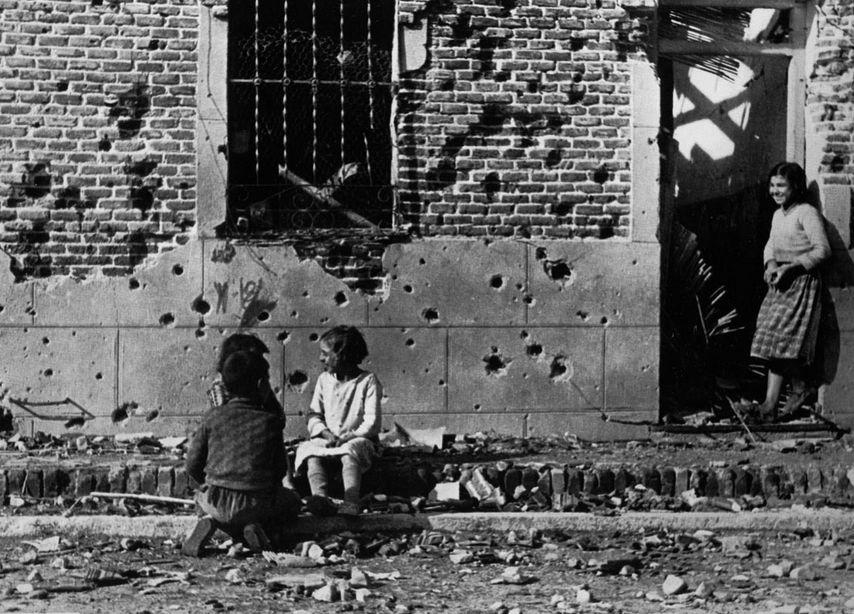 Fotografía de Robert Capa. Los niños ríen ajenos a la guerra ante la fachada destrozada por la metralla del número 10 de la calle Peironcely, November-December 1936 ©International Center of Photography/Magnum Photos.